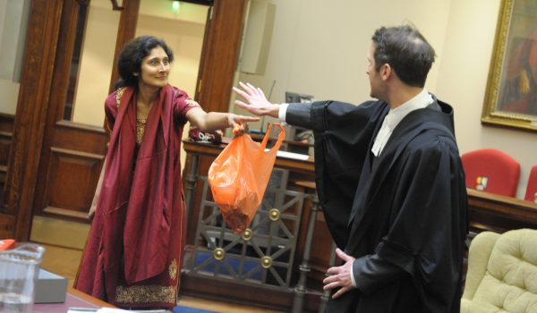 a woman pointing angrily at a barrister