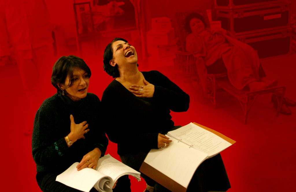 two women reading scripts laughing